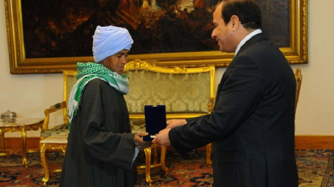 Egyptian President Abdel Fatah al-Sisi hands Sisa Abu Daooh the motherhood award. (Courtesy: Guardian newspaper)